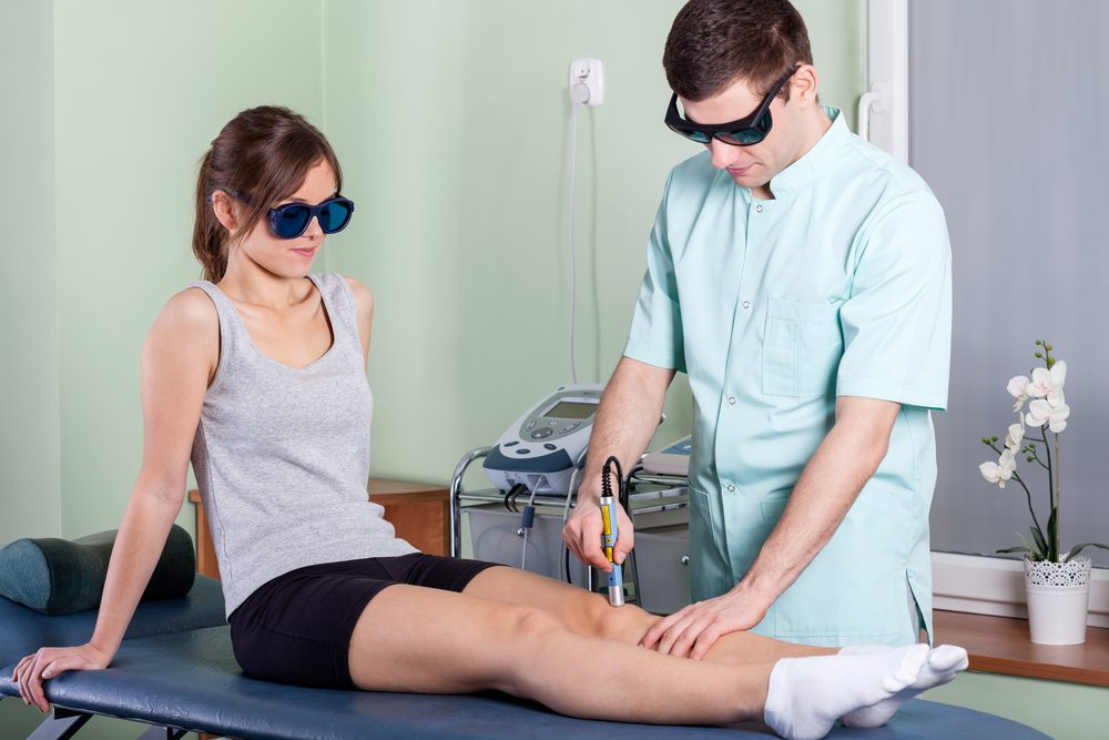 A doctor performing laser treatment on a patient's knee
